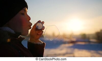 boy blows soap bubbles in the Park with delight at winter sunset