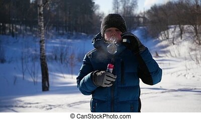 boy blows soap bubbles in the Park with delight on a winter Sunny day