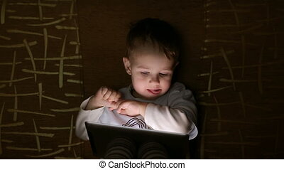 boy browsing tablet pc in the dark