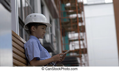 boy builder sits on the bench uses a tablet, monitors the builder project, plays a builder
