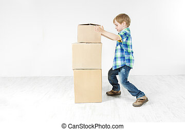 Boy building pyramid of carton boxes. Packing up to move. Growth concept.
