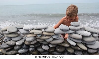 boy building wall of stones on beach, sea surf in background