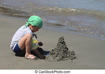 boy builds a sand castle,
