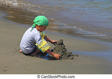boy builds a sand castle