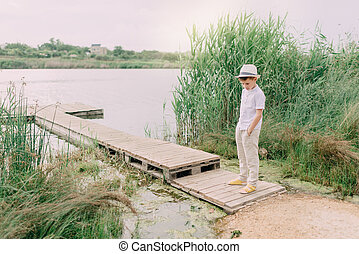 boy by the river and reed