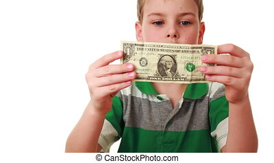 boy carefully studies bill denominations of one dollar - boy...