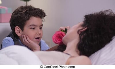 Boy caressing sleeping mom's face with rose - Close up...