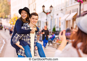 Boy carrying laughing woman and girl shooting them