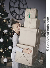 Boy carrying stack of gifts