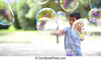 Boy Catching Soap Bubbles - Boy catching soap bubbles in a...
