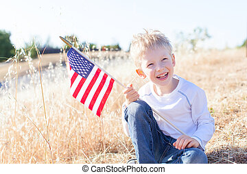 boy celebrating 4th of July - little boy holding american...