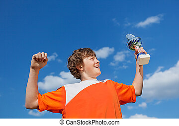Boy Celebrating Victory While Holding Trophy Against Sky