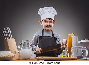 Boy Chef Cooking on a gray background. - Kid Chef with a pan...
