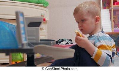 Boy chews sandwich profile portrait childrens room home interior