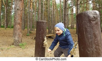 Boy child blond rocking wooden board. Little boy on the playground in the park. A cloudy fall day