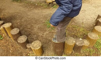 Boy child blond walking on stumps. The little boy is training to keep his balance. A cloudy fall day