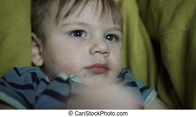 Boy child with food leftovers on his face on frameless furniture on the floor watching TV