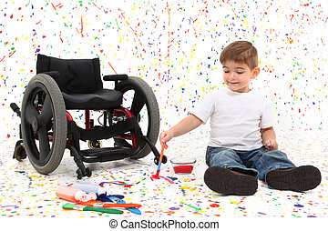 Adorable 2 year old child with wheelchair painting on floor.