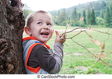 Boy child playing outdoors branch.