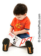 Addorable Toddler Boy Reading Alphabet Book. Book pages created in photoshop. Shot in studio over white.