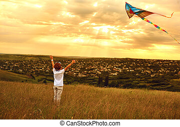 Boy child runs with a kite on the field.