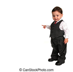 Small child in a business suit pointing to the side while looking at the camera.
