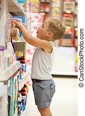 Boy choosing toy in the shop - Little boy choosing toys on...