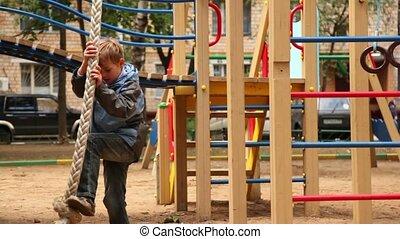 Boy climb on rope at playground