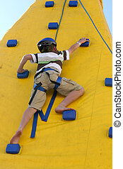 Boy climbing a climbing wall.