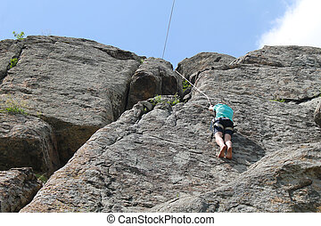 Boy climbing on the rock