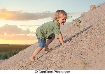 Boy Climbing On The Sand dune. Summer day