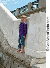 Boy climbing on wall barefoot
