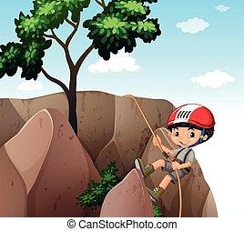 Boy climbing up the cliff