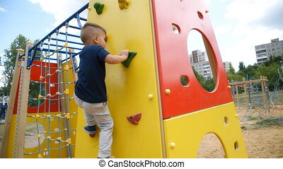 boy climbs up the climbing wall on the playground in summer...