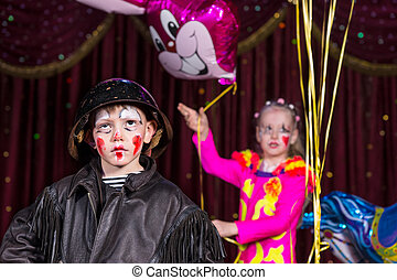 Boy Clown on Stage with Girl Holding Balloons