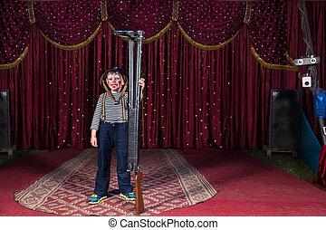 Boy Clown Wearing Helmet Holding Gun on Stage