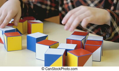 Boy collecting a pattern using colored cubes - Little boy ...