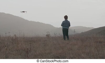 Boy controls drone amid hills