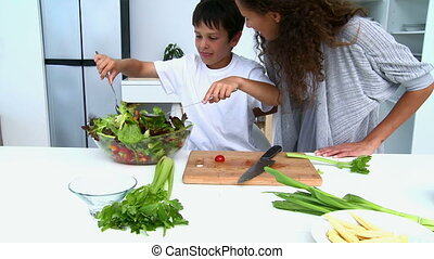 Boy cooking a salad with his mother