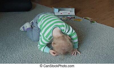 Boy crawling on a light carpet