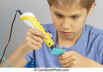 Boy creating with 3d printing pen new object