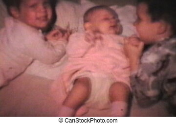 Boy Cuddles Baby Sister (1968) - A proud big brother cuddles...