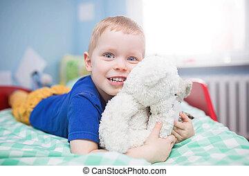 Boy cuddling his mascots