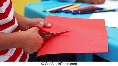 Boy cutting paper shapes classroom