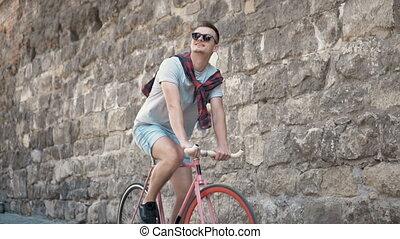 Boy Cycles near Wall - Cheerful caucasian boy cycling next...