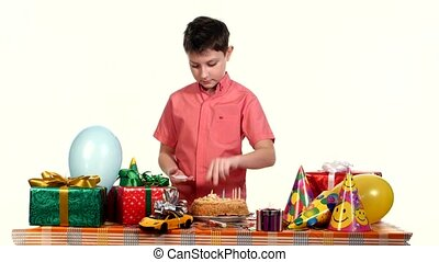 Boy decorated birthday cake candles. Table strewn with gifts and balloons. white background
