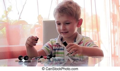 boy design machine from colored toy pieces