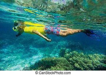 Boy dives in a tropical sea