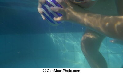 Boy diving and coming up from water in the pool