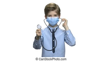 Boy doctor in surgical mask holding stethoscope.
